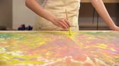 многоцветный : Close-up of female artist in apron working on abstract painting in her studio