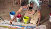 pędzel : Talented painter sitting on floor at his studio and splattering colorful acrylic paints onto canvas Wideo