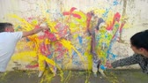 красочный : Time lapse of two street artists creating a colorful abstract mural by splashing acrylic paints on a wall and two models in protective coveralls to leave white silhouettes on multi-colored wall Стоковые видеозаписи