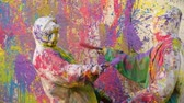 malovat : Medium shot of two painters in protective coveralls and respirators stroking each other with colorful paint against paint splattered wall Dostupné videozáznamy