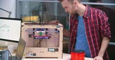 plástico : Young designer controlling a 3d printer making three-dimensional plastic objects Stock Footage