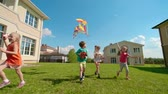 красочный : Four kids are running on green grass: two girls flying kites, boys holding wooden toys