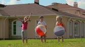 inflável : Kids tossing big colorful beach balls in the air while playing in the backyard