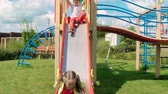 красочный : Happy girl and two boys riding down on slide one by one on playground and running Стоковые видеозаписи