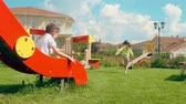 prato : Kids riding down on slide and running to seesaw in the playground Stock Footage