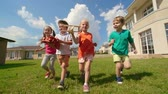 транспорт : Four happy kids running towards the camera on green grass and holding wooden toys