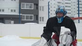 captura : Ice hockey goaltender stopping a puck from going into his goal net during a play at outdoor rink