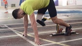 bloco : Slow motion shot of determined athlete with prosthetic leg starting from blockson track