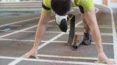 нога : Young athlete with artificial leg starting from blockson track in slow motion