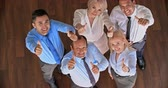 diretamente acima : High angle view of smiling business team raising their hands up and showing thumbs up
