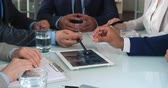 informace : Close up of businessmen hands using tablet to work with financial diagrams on the meeting