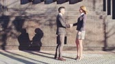 handshake : Businesswoman walking on the street towards her male colleague, they shaking hands and talking Stock Footage