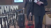 bagagem : Tilt up of businesswoman and businessman walking with suitcases in hotel lobby