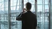 беспроводной : Rear view of businessman standing in modern glass elevator and talking on the phone