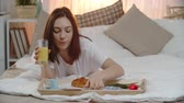 tulip : Beautiful woman lying in her bed, reading letter from secret admirer and smelling red tulip while eating croissant and drinking orange juice for breakfast