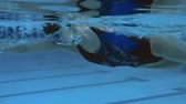 à beira da piscina : Underwater view of professional female swimmer performing front crawl in swimming pool