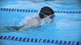 borboleta : Side view of sportswoman in cap and goggles swimming butterfly stroke in pool in slow motion