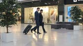 aeroporto : Two young Asian businessmen walking across duty free zone at airport, one of them pulling suitcase, another man checking time; slow motion shot on Sony NEX 700