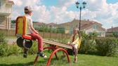 dzieci : Little boy and girl enjoying riding seesaw on green lawn in slow motion Wideo