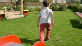 яркий : Rear view of little boy and girl riding slide and running to seesaw through green lawn on playground