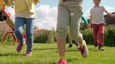 arbusto : Two excited little girls and two boys running through green lawn towards the camera and holding hands Stock Footage