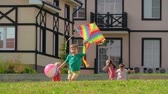 красочный : Four children running barefoot on green lawn: one boy flying kite and little girl holding colorful inflatable ball