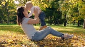 mama : Mother sitting on the lawn in park on golden leaves, holding her little child and lifting him up