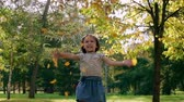 движение : Excited little girl tossing pile of golden leaves in the air in the park in slow motion