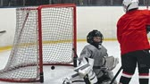 ponto : Little hockey player handling the puck and scoring the goal while playing on the ice rink Stock Footage