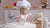 avental : Little girl in apron and chef hat preparing flour to make pastry: she making well with egg and using knife to smooth edges