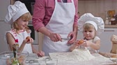dough : Father breaking egg with knife and giving it his little daughter; she adding it to flour on the table and her sister helping to mix ingredients for dough