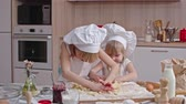 farinha : Two little girls in white aprons and hats with flour on their faces kneading dough together on kitchen table