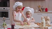 avental : Two little sisters cutting out cookies from dough using metal cutters on the kitchen table
