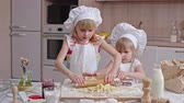 avental : Two adorable little sisters dressed like restaurant chef preparing dough using rolling pin in the kitchen Stock Footage