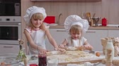 farinha : Two beautiful little girls shaping dough with rolling pin on wooden cutting board