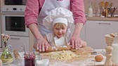 dough : Dad helping his little daughter to knead the dough with rolling pin in the home kitchen Stock Footage