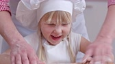 avental : Close up of little cute girl with flour on her face using rolling pin for cooking with assistance of her dad