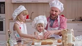 farinha : Lovely family spending their leisure time in the kitchen: dad and two little daughters enjoying cutting out cookies from dough together