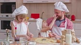 farinha : Dad and two adorable daughters making cookies together at home: man kissing one of girls and she putting some flour on her nose and laughing Stock Footage