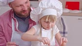 dough : Cute little girl in chef hat and apron decorating cookie dough with berries while her father standing behind her and telling an advice