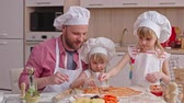 avental : Dad telling their little daughters how to smooth sauce over dough base of pizza while cooking together in the kitchen Stock Footage