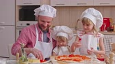 hat : Dad giving slices of tomato and ham to his daughters and girls putting them on pizza dough