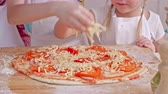 pizza cheese : Cute little girl eating grated cheese while sprinkling it on homemade pizza; male hand putting basil on top of pizza Stock Footage