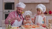 pizza cheese : Daddy and two little girls in chef hats and aprons sprinkling pizza with cheese before baking it Stock Footage