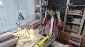 tesař : Young Asian craftswoman using planer machine to cut wood in her small woodworking studio