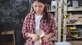 pastime : Medium tilt down shot of young Asian craftswoman drinking tea and listening to music with earphones while making paper mache animal toys at her handmade studio