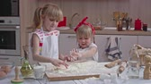 avental : Two little blonde sisters in aprons standing together in the kitchen and playing with flour on the table