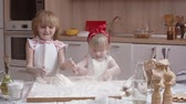 стол : Cute little sisters having fun in the kitchen: they tossing baking flour in the air and playing with it