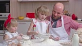 farinha : Man siting the flour and his little daughters shaking it with metal sieves