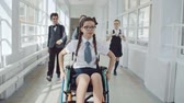 classmates : Disabled girl riding wheelchair at school while her friends running through corridor to help her